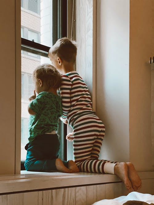 Two Boys Looking Outside Window