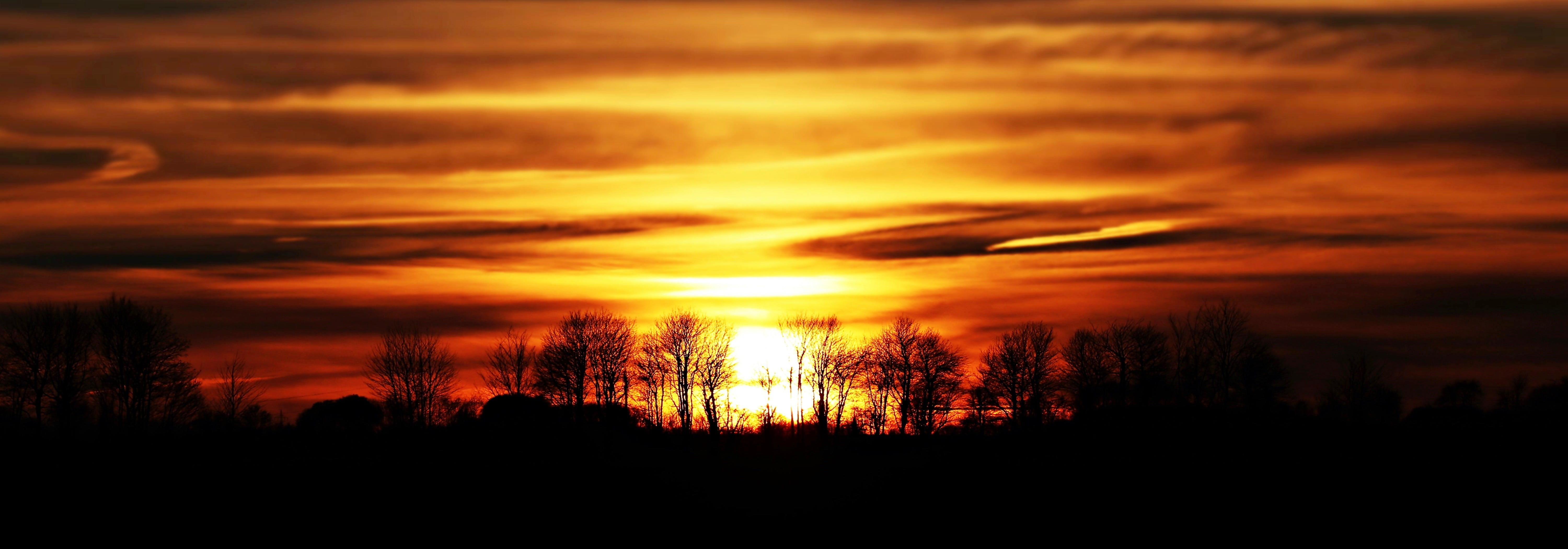 Scenic View of Silhouette Landscape Against Sunset Sky