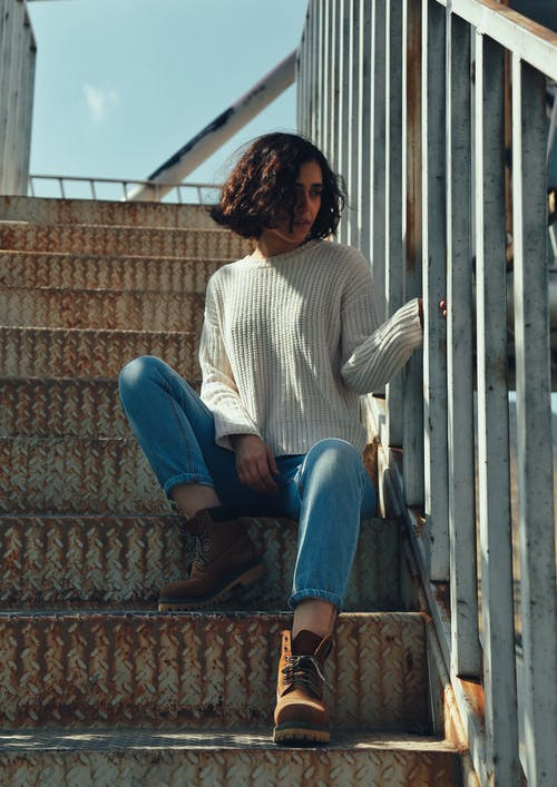 Woman Wearing White Sweater and Blue Jeans Sitting on Stairs
