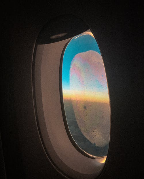 Free stock photo of airplane window, flight, frost on window, over the clouds