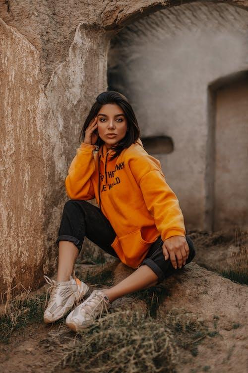 Woman Wearing Orange Pullover Hoodie and Black Capri Pants