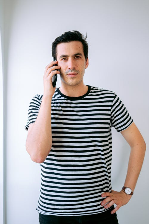 Man Wearing Stripped T-shirt Holding Phone on His Ear