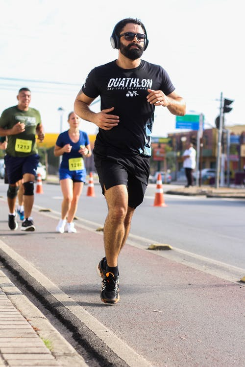 Man Wearing Black Crew-neck T-shirt and Black Short Running Marathon on Sidewalk