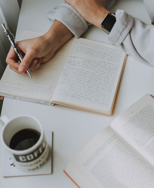 Person Writing on Notebook