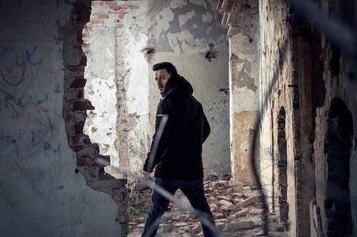 Man Looking over His Left Shoulder Inside Abandoned Building