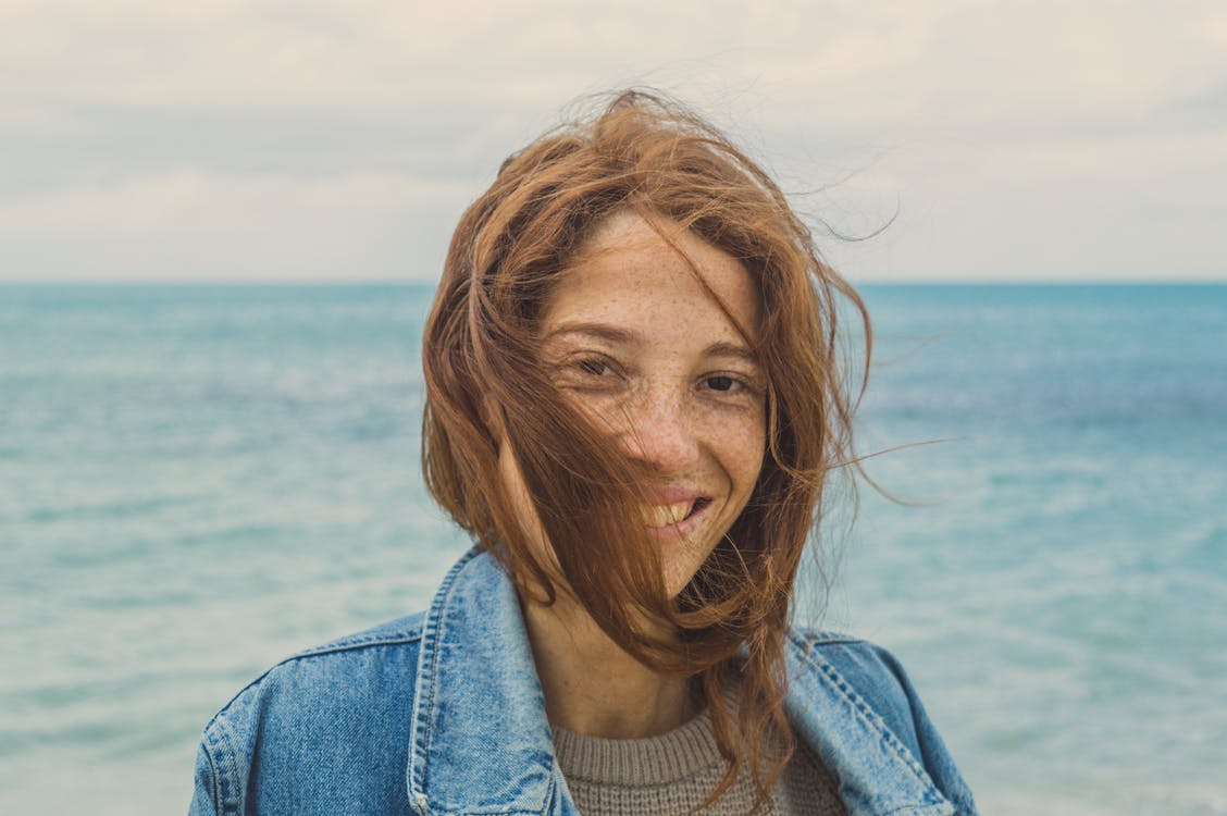 Portrait Photo of Smiling Woman with brown Hair Near Body of Water