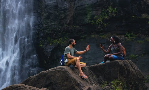 Man and Woman Talking Near Waterfalls