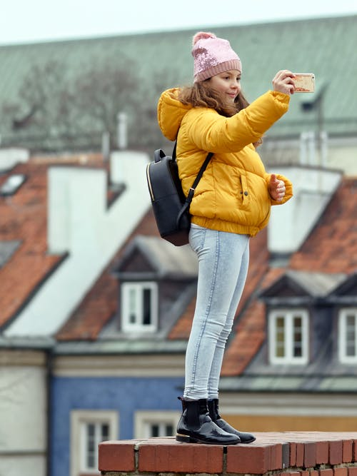 Woman in Yellow Puffer Jacket and Blue Jeans Holding Smartphone