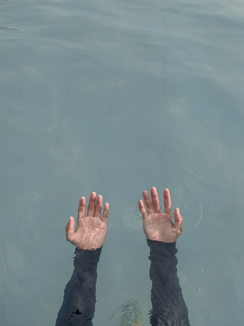 Person's Hand on Water