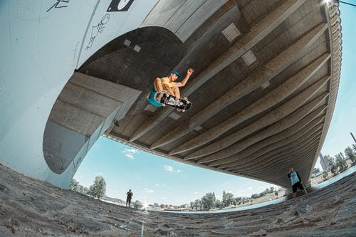 Fish Eye Photography of Man Doing Skateboard Trick