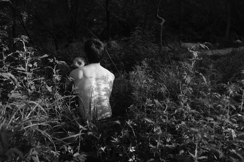 Grayscale Photo of Topless Man Near Plants