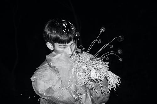 Grayscale Photo of Boy in White Dress Shirt Holding Flowers