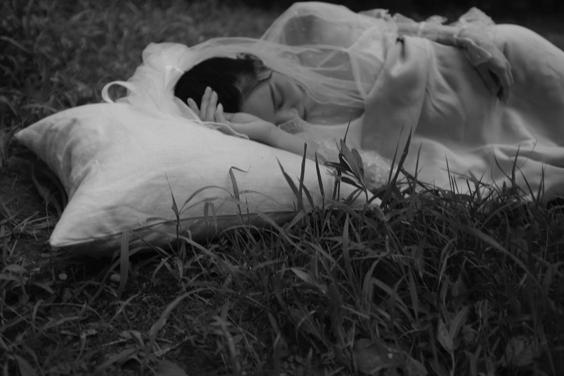 Grayscale Photo of Woman Lying on Grass Field