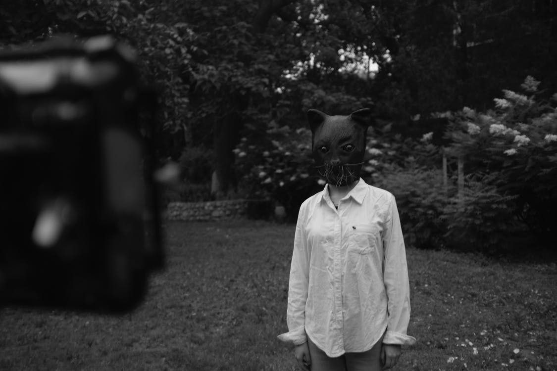Grayscale Photo of Person Wearing Cat Mask