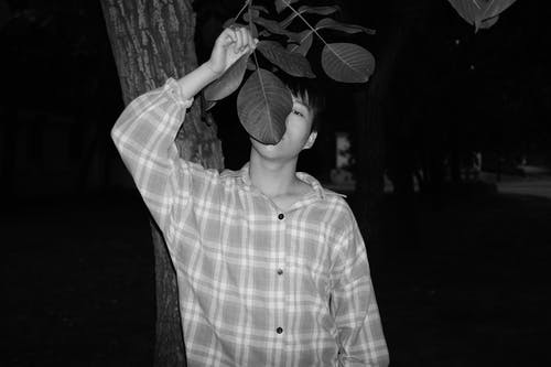 Grayscale Photo of Man in Grid Button-up Shirt Under Tre