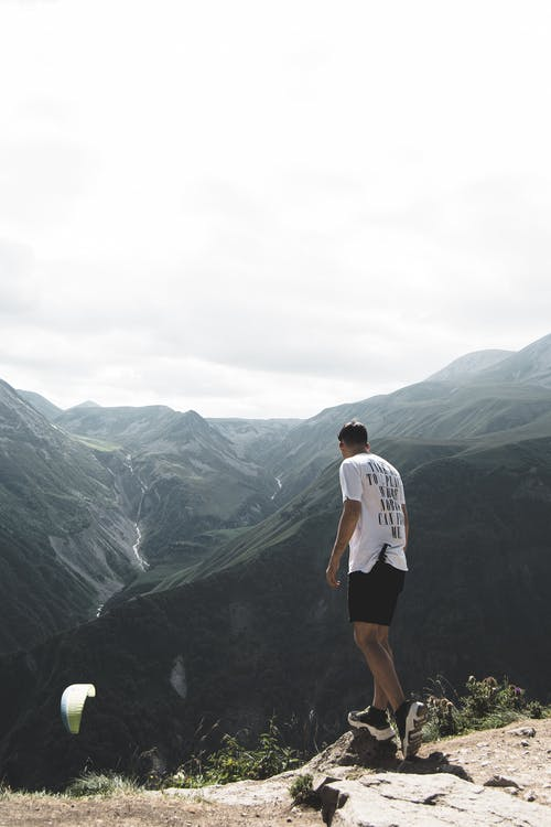 Man Wearing White T-shirt and Black Shorts Standing on Cliff
