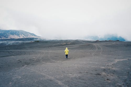 Person Wearing Yellow Hoodie Standing on Sand