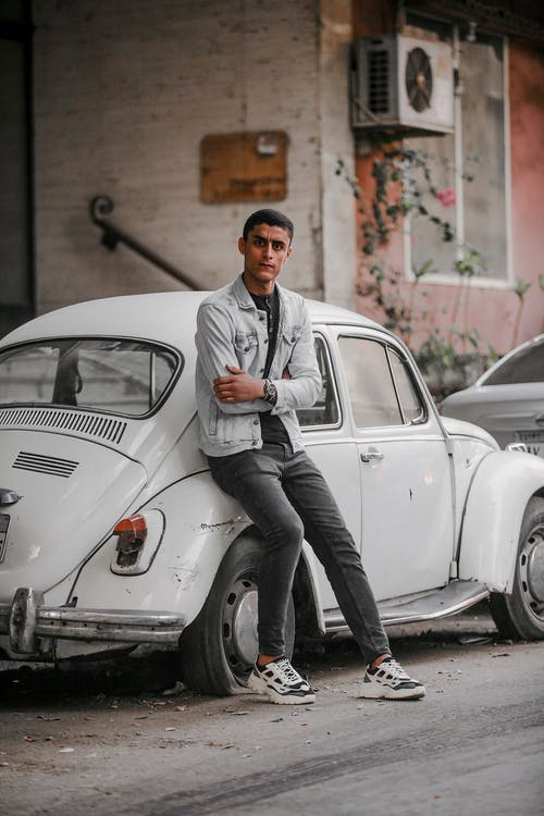 Man Leaning on White Volkswagen Beetle