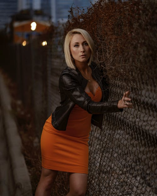 Woman Leaning Against Gray Wire Fence