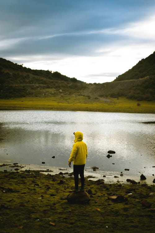 Man in Yellow Hoodie Standing on Brown Rock Near Lake