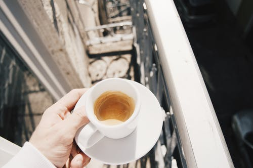 Crop person with cup of coffee on balcony
