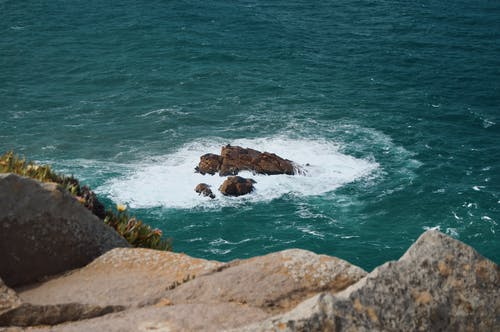 Photo Of Rock Formation On Sea During Daytime