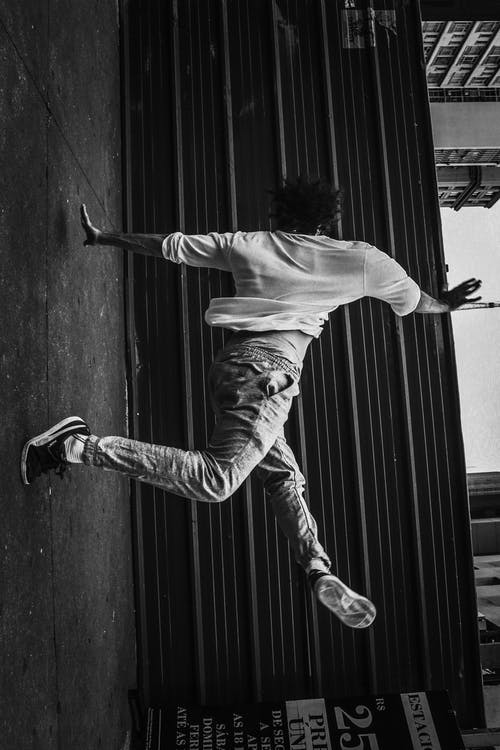 Man in White Shirt and Gray Pants Jumping on Black Wooden Wall