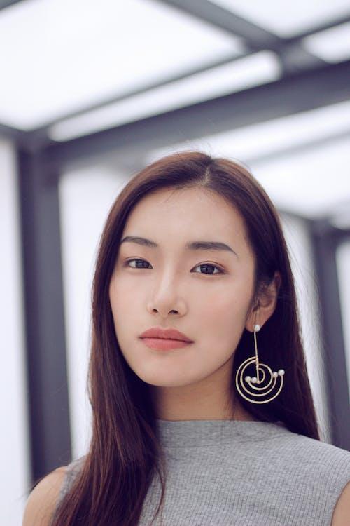 Woman Wearing Silver-colored Drop Earring