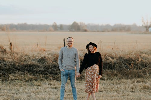 Photo of Smiling Couple Standing on Brown Grass Field While Holding Hands
