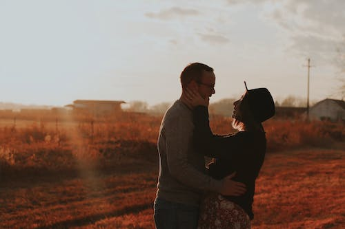 Side View Photo of Hugging Couple Standing on Brown Grass Field at Golden Hour