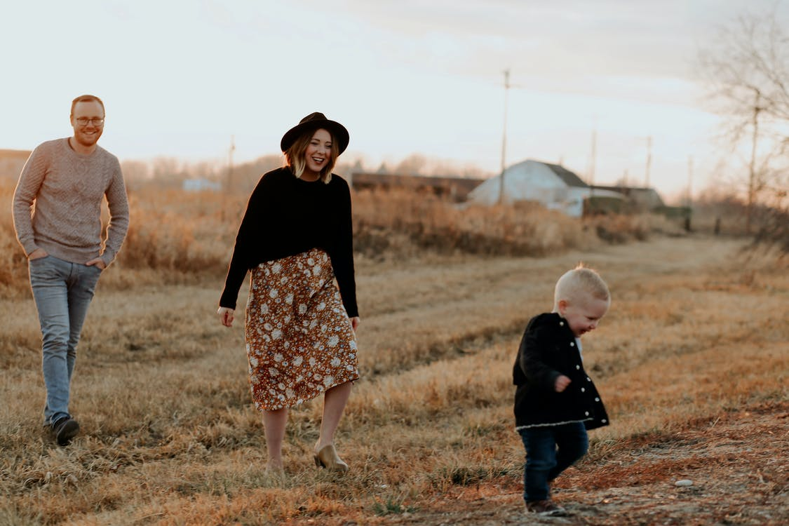 Couple and a Child Walking on Brown Grass
