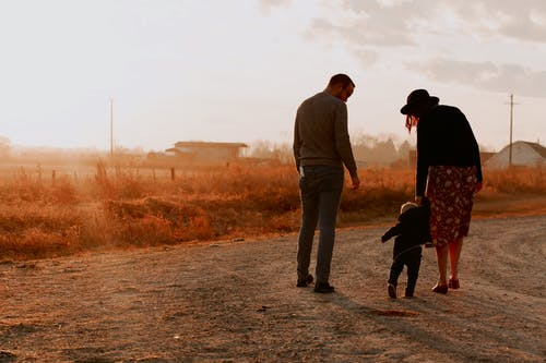 Man and Woman Walking with There Kid on Dirt Road