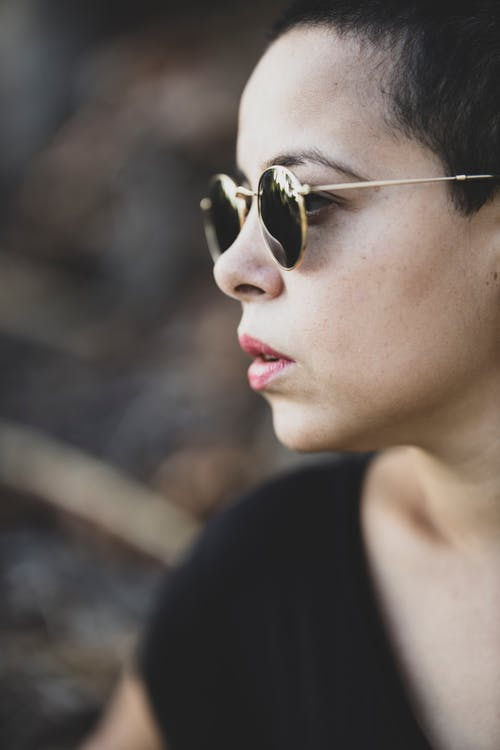 Shallow Focus Photo of Person Wearing Black Sunglasses