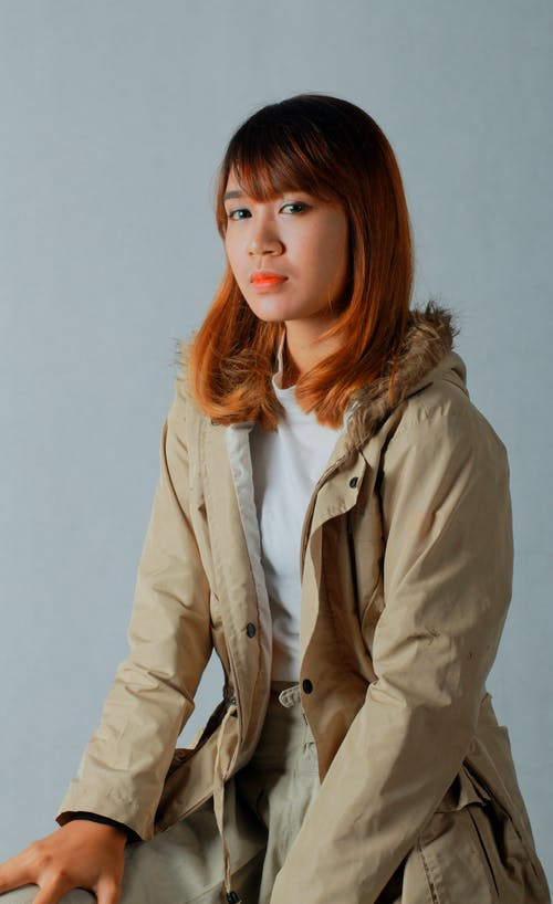 Woman With Blonde Hair Wearing A Beige Jacket