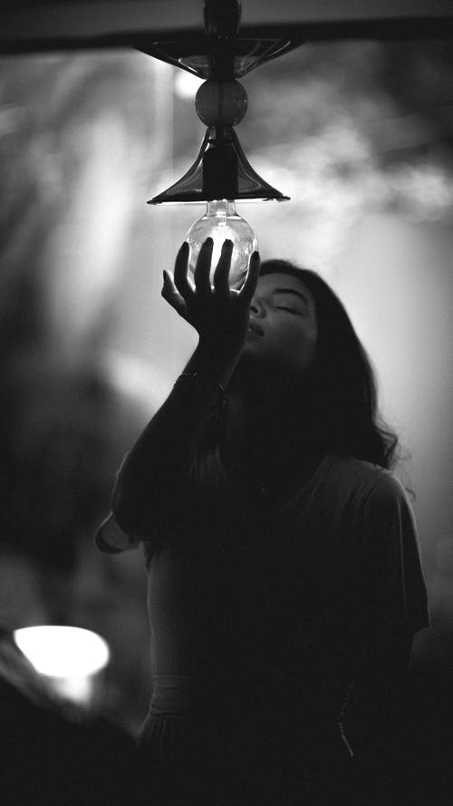 Grayscale Photo of Person Holding Light Bulb
