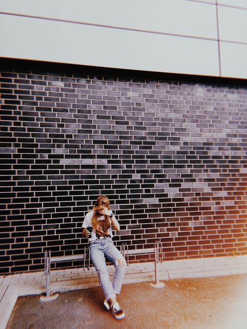 Woman Sitting on Bench Beside Wall