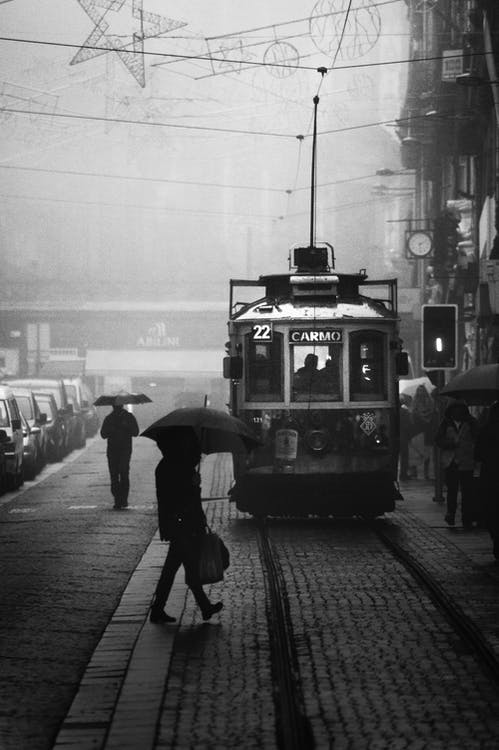 Grayscale Photography of Person Crossing Street Near a Tram