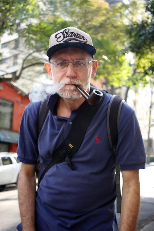 Man in Blue Polo Shirt Smoking Outdoors