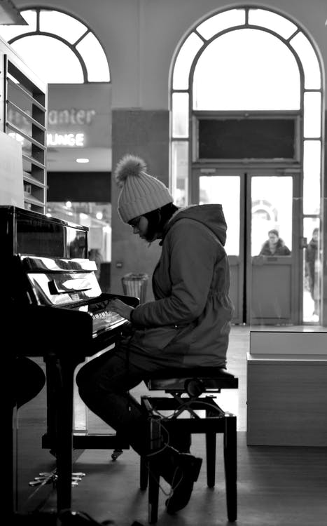 Grayscale Photography of Woman Sitting in Front of a Piano