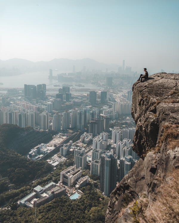 Man Sitting on Mountain Overviewing Metropolitan Building