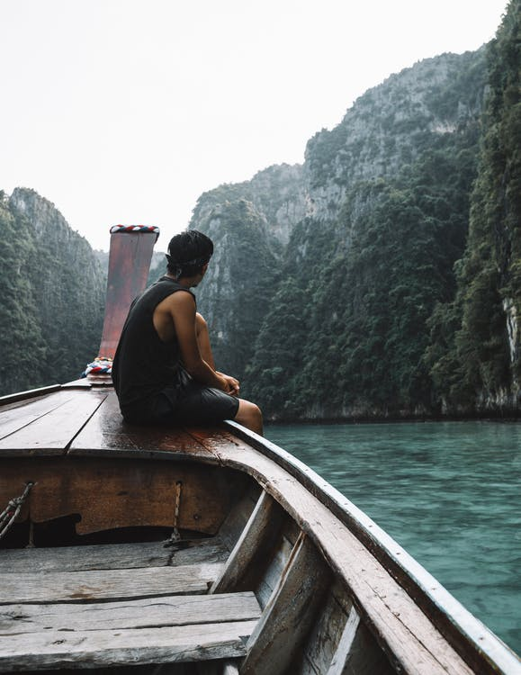 Man Sitting on Sailboat