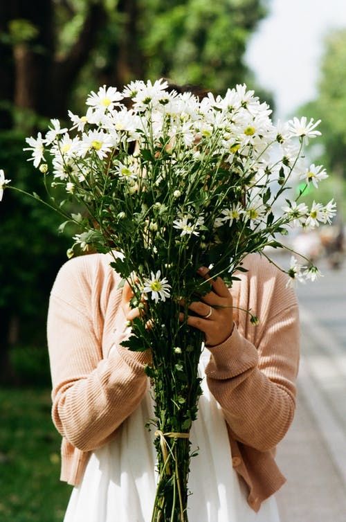 Woman in Cardigan Holding White Flowers
