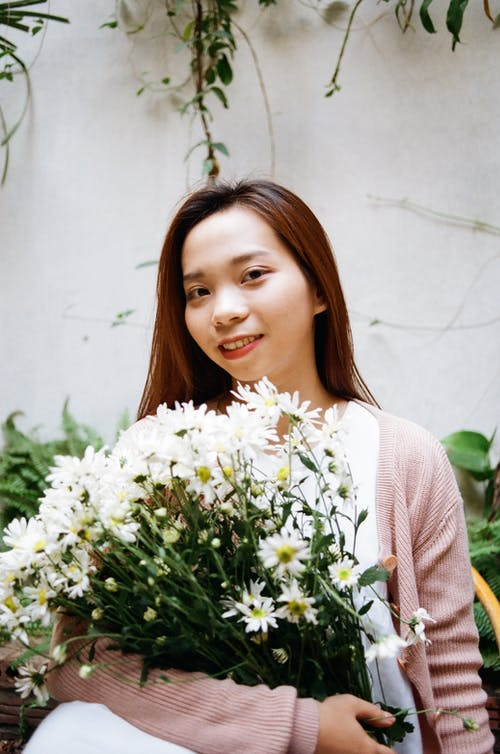 Woman in White Top and Pink Cardigan Holding White Daisy Flower Bouquet