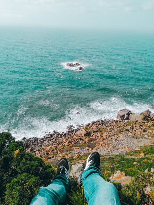 Person in Black Pants and Black Hiking Shoes Sitting on Rocky Shore