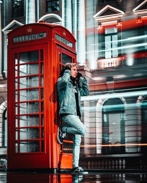 Foto Van Man Leunend Naast Rode Telefooncel