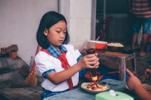 Girl Putting Ketchup on Food