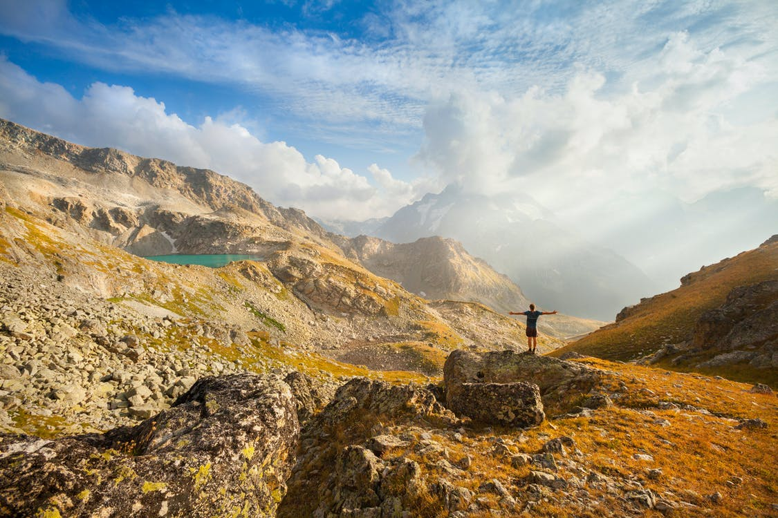 Standing Man on Mountain in Front of Lake