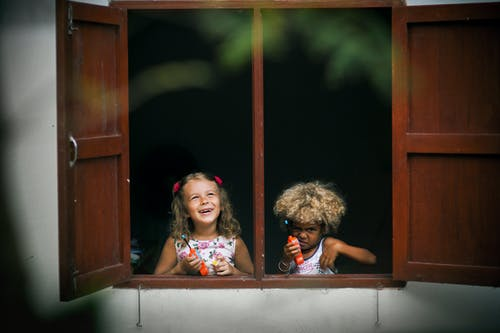 Selective Focus Photography of Two Girls on Window