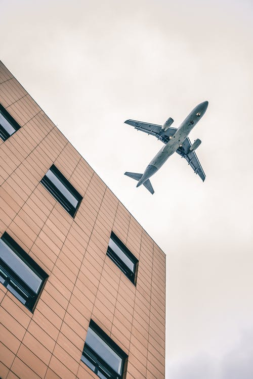 Low-angle Photography of Brown High-rise Building Showing Blue Airplane in the Sky