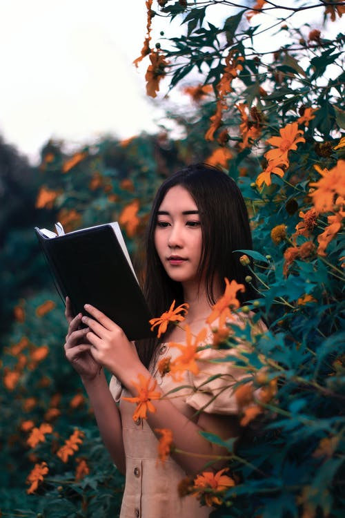 Woman Reading Book Surrounded by Plants